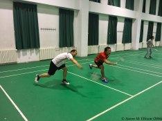 Professor Lu (left) and badminton partner lunge for the birdie